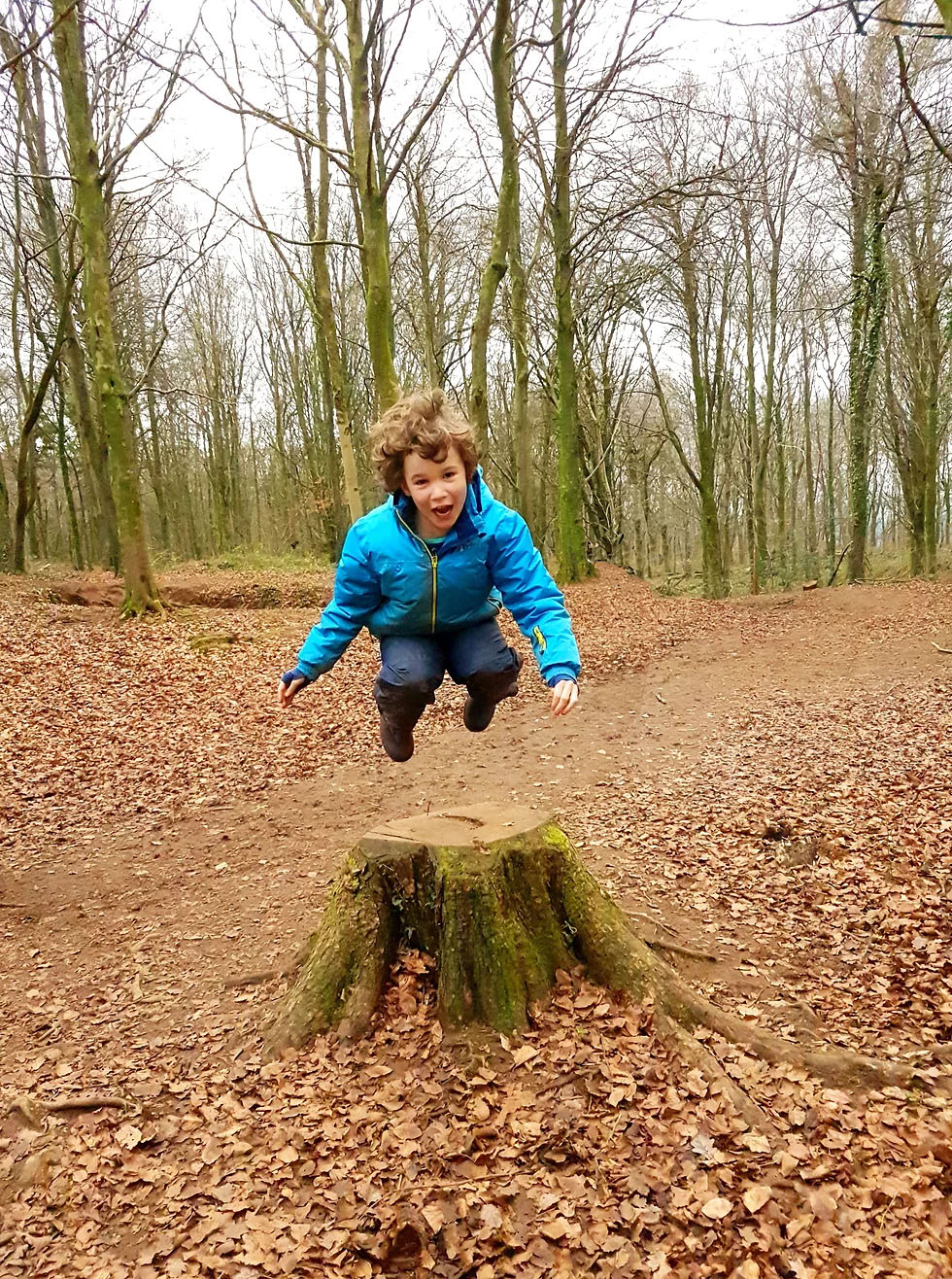child leaping over a stump