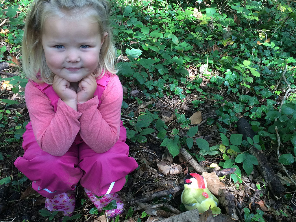 little girl crouching on forest floor