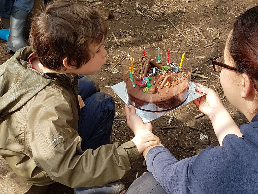 boy getting a birthday cake in the forest