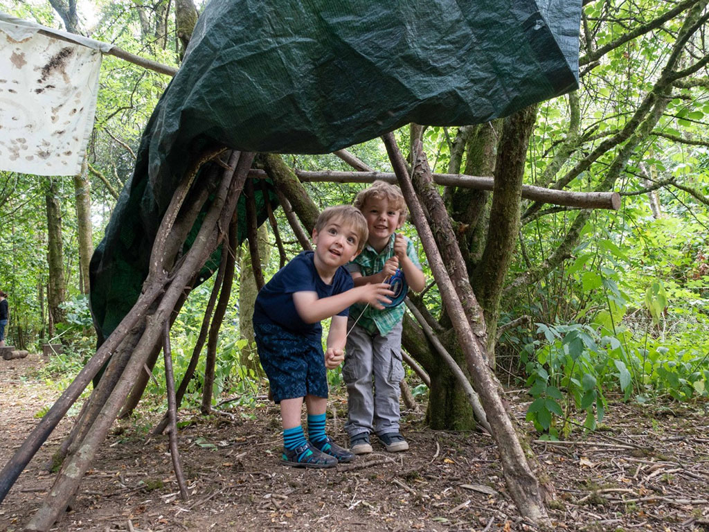 two children under a shelter made of sticks